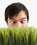 Cross-eyed man behind grass.