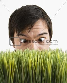 Cross-eyed man behind grass.