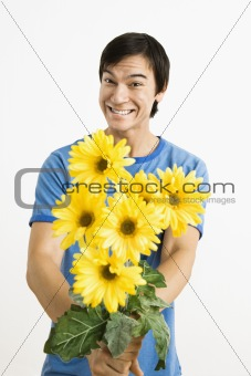 Smiling man holding bouquet.