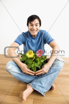 Man holding flower plant.