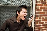 Man screaming at cell phone.
