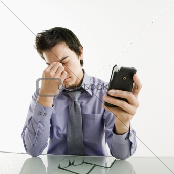 Tired businessman with cell phone.