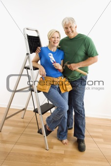 Man and woman with tools and ladder.