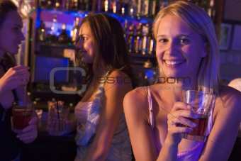 Three young women enjoying drinks at a nightclub