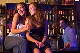 Two young women sitting on a bar counter, enjoying cocktails