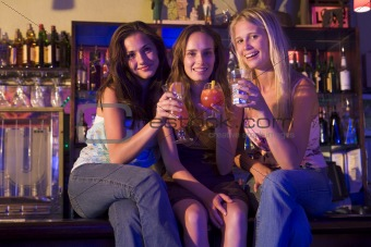 Three young women sitting on a bar counter, enjoying cocktails