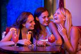Three young women sitting at a table and laughing in a nightclub