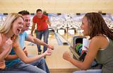 Four young adults cheering in a bowling alley