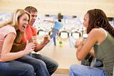 Young adults cheering in a bowling alley