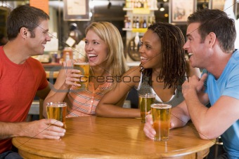 Group of young friends drinking and laughing in a bar