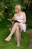 cute blond reads book in garden