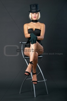 Variety show woman sits on bar chair.