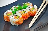 Sushi California Philly rolls appetizer with rice, avocado, and salmon on blue plate w/ chopsticks.