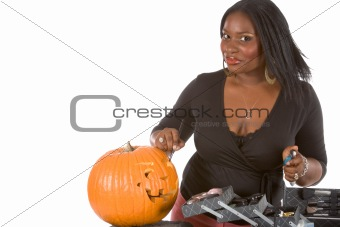 Black make-up artist decorating Halloween pumpkin