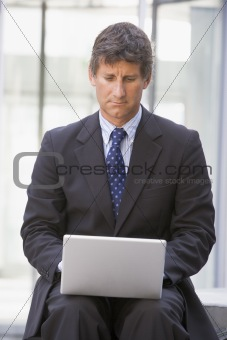 Businessman sitting in office lobby using laptop