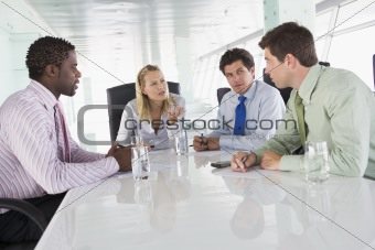 Four businesspeople in a boardroom talking