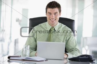 Businessman sitting in office with personal organizer using lapt