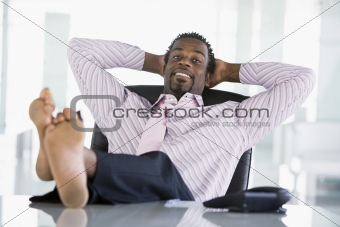 Businessman sitting in office with feet on desk relaxing and smi