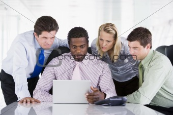 Four businesspeople in a boardroom looking at laptop