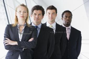 Four businesspeople standing in corridor