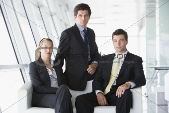 Three businesspeople sitting in office lobby