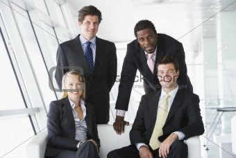 Four businesspeople in office lobby smiling
