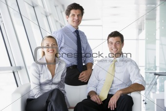 Three businesspeople sitting in office lobby smiling