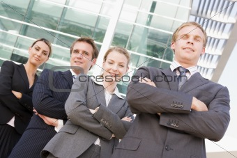 Four businesspeople standing outdoors smiling