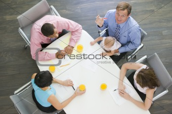 Four businesspeople in boardroom with one holding a baby