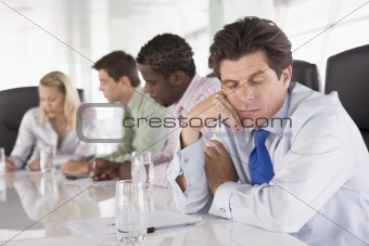 Four businesspeople in boardroom with one businessman sleeping