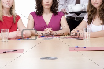 Three businesswomen sitting in boardroom being served coffee and