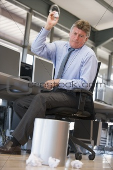 Businessman in office space throwing garbage in bin