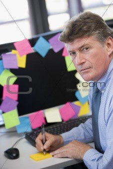 Businessman in office at monitor with notes on it writing