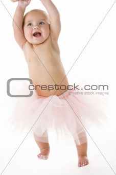 Baby standing in tutu