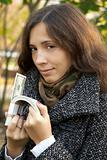 young girl holding roll of dollars