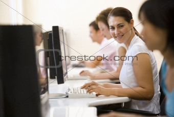 Four people sitting in computer room typing and smiling