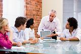 Five businesspeople in boardroom with laptop