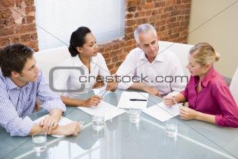 Four businesspeople in boardroom talking