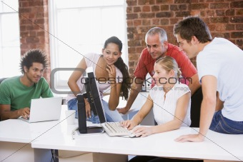 Five businesspeople in office space looking at computer and smil