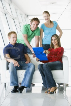 Four people in lobby pointing at clipboard smiling