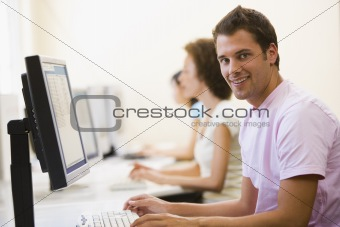 Three people sitting in computer room typing and smiling