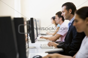 Four people sitting in computer room typing with one man in a su