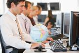 Five businesspeople in office space with a desk globe in foregro
