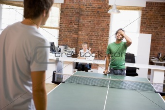 Two men in office space playing ping pong