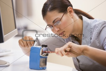 Woman in computer room using pencil sharpener