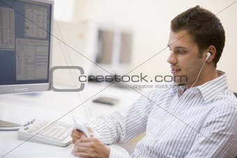 Man in computer room listening to MP3 player
