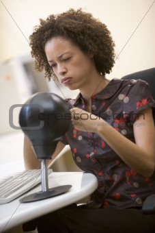 Woman sitting in computer room punching a small punching bag