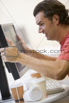 Man in computer room with many empty cups of coffee grabbing his