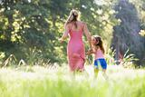 Woman and young girl running outdoors holding hands and smiling