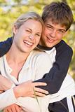 Woman and young boy embracing outdoors and smiling